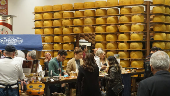 A room with walls made out of cheese rounds drew in show attendees at Gourmet Foods International's booth at Winter Fancy Food Show.