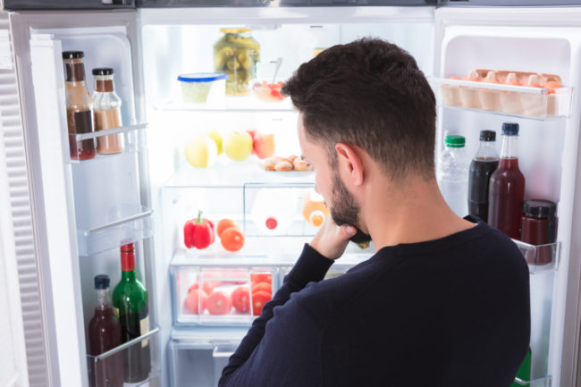 Man looking in fridge wondering what's for dinner