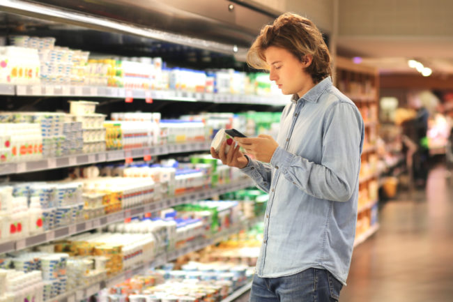 Gen Z guy reading food label at supermarket