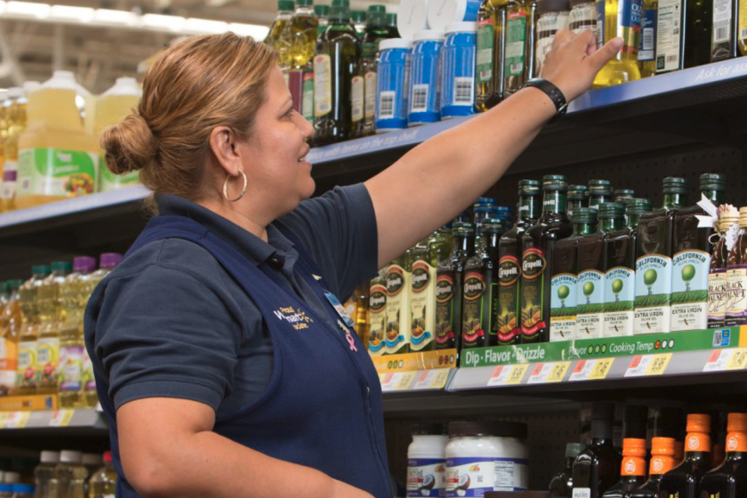 Walmart employee stocking shelves with olive oil