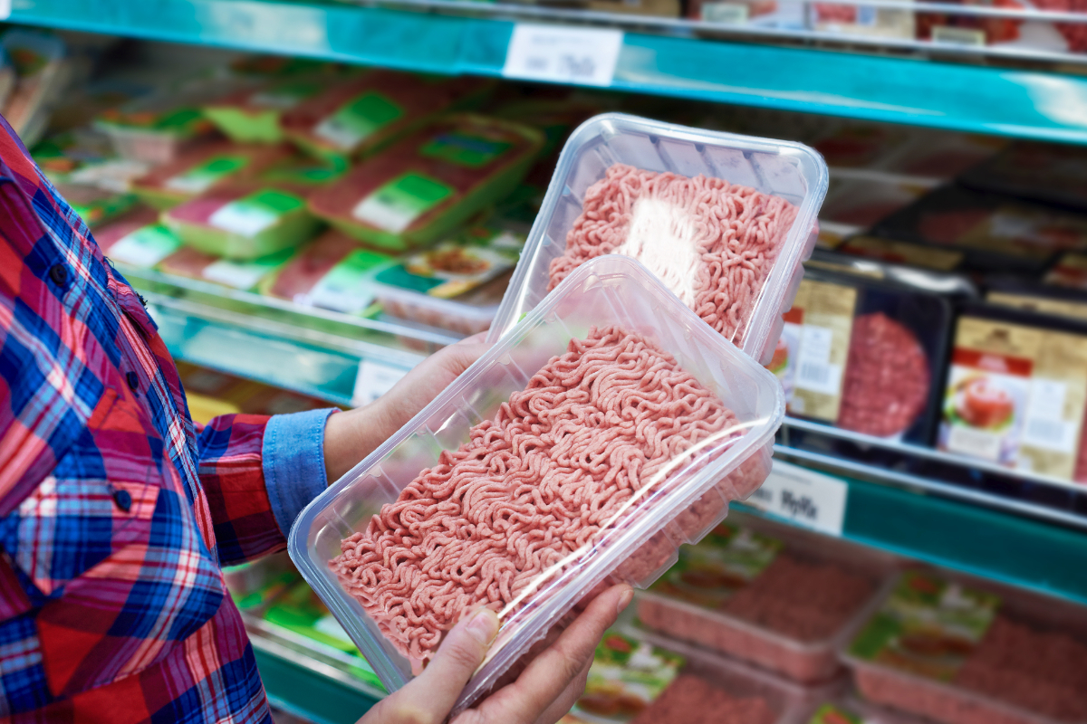 Grocery shopper choosing between two ground meat options