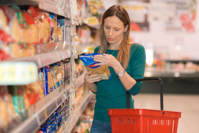 Woman reading pasta label in supermarket