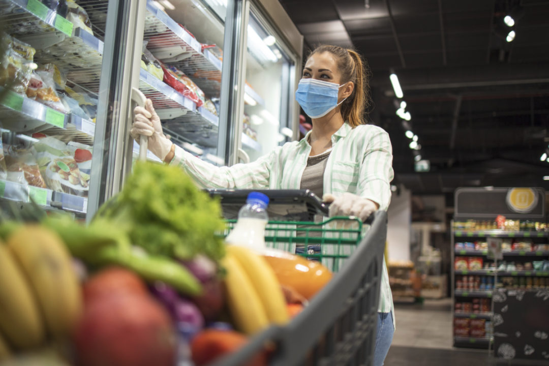 Woman grocery shopping while wearing face mask and gloves