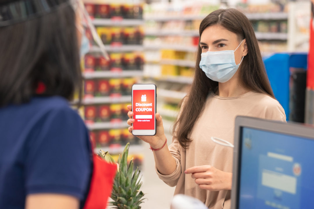 Woman with face mask using digital grocery coupon