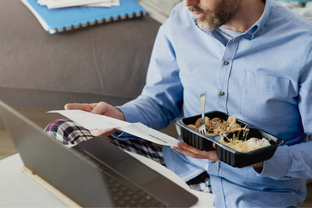 Man working from home and eating a microwaved meal