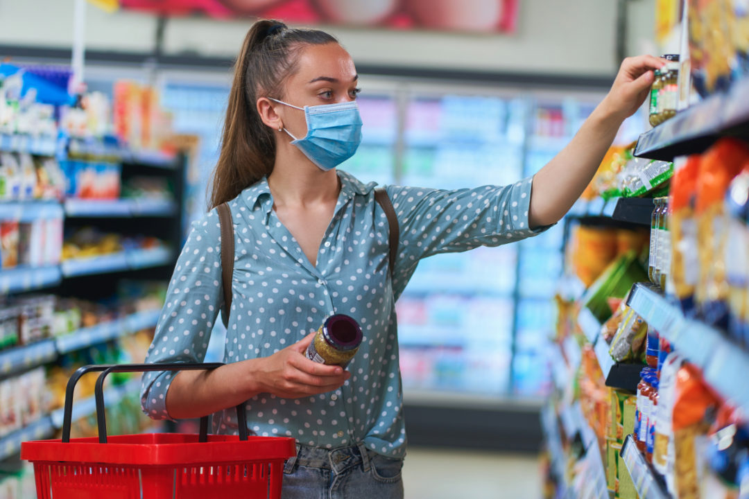 Woman wearing mask while grocery shopping during coronavirus pandemic
