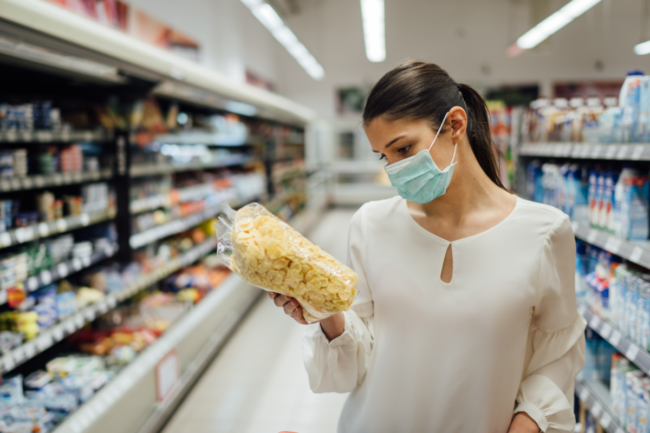Woman grocery shopping while wearing a protective face mask