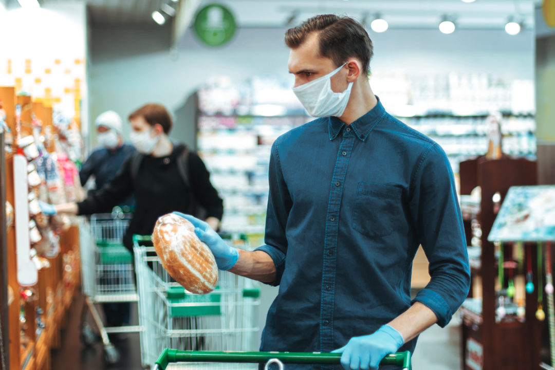 Man wearing face mask shopping for bread in a supermarket