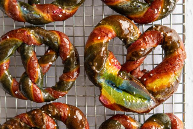 Jumbo rainbow colored pretzels on cooling rack