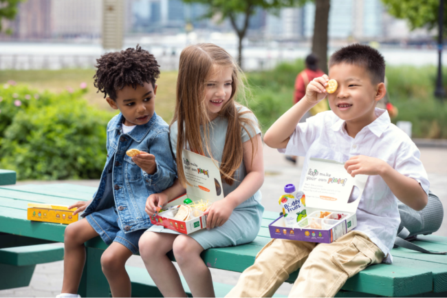 Children eating plant-based lunch kits from Lets Plate